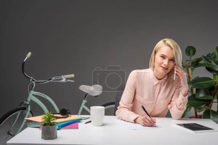 portrait of businesswoman talking on smartphone while making notes at workplace