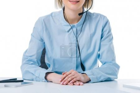 partial view of call center operator in headset at workplace isolated on white
