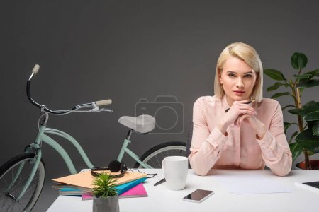 portrait of pensive businesswoman at workplace with documents, smartphone and cup of coffee