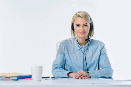 portrait of young smiling call center operator in headset at workplace