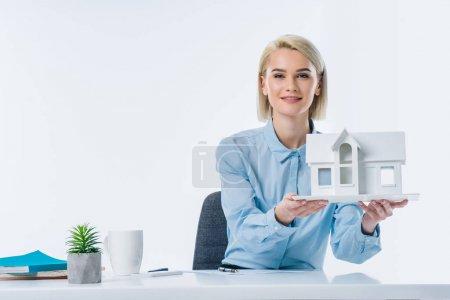 Photo pour Portrait de l'agent immobilier montrant la maison modèle au milieu de travail - image libre de droit