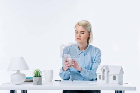 Photo pour Portrait de l'agent immobilier à l'aide de smartphone sur lieu de travail avec la maison modèle - image libre de droit