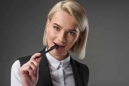 portrait of beautiful young businesswoman with pen isolated on grey