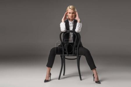young stylish woman sitting on chair and looking at camera isolated on grey