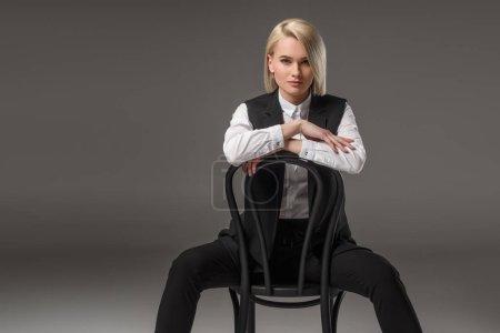 Foto de Retrato de mujer joven y elegante sentada en la silla y mirando a la cámara aislada en gris - Imagen libre de derechos