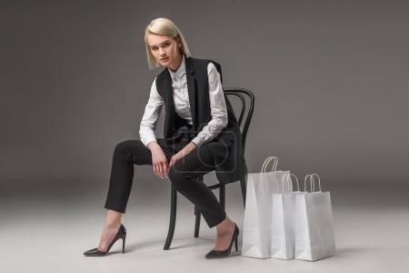 Photo pour Femme élégante assise sur une chaise près de sacs à provisions - image libre de droit