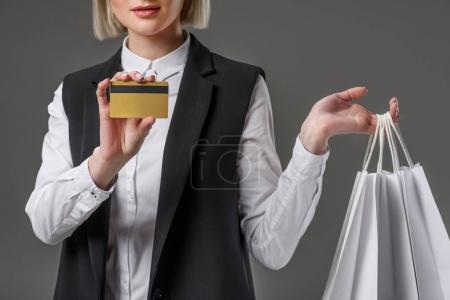 cropped shot of stylish woman with credit card and shopping bags isolated on grey
