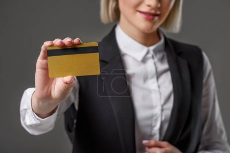 cropped shot of woman showing credit card in hand isolated on grey