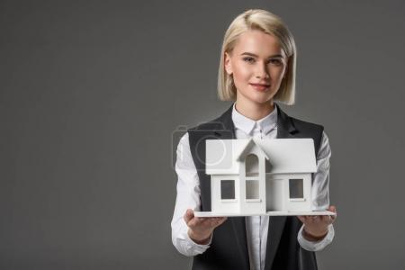 portrait of young real estate agent with house model isolated on grey