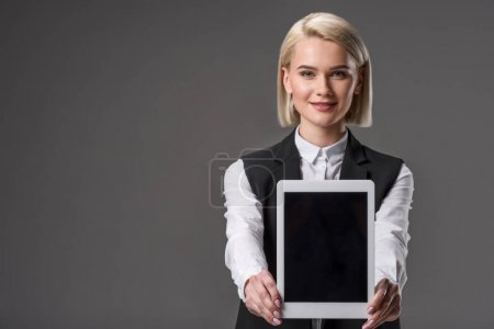 Photo for Portrait of smiling woman showing tablet with blank screen isolated on grey - Royalty Free Image