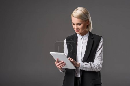 Photo for Portrait of young woman using tablet isolated on grey - Royalty Free Image
