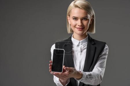 Photo for Portrait of smiling woman showing smartphone with blank screen isolated on grey - Royalty Free Image