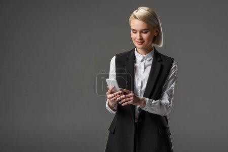 Photo pour Portrait de jolie femme à l'aide de smartphone isolé sur fond gris - image libre de droit