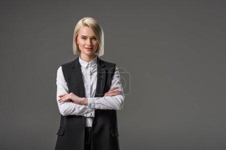Foto de Retrato de moda mujer con los brazos cruzados mirando a cámara aislada en gris - Imagen libre de derechos