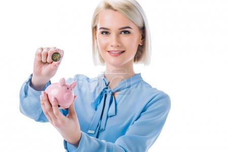 Porträt einer lächelnden Geschäftsfrau mit Sparschwein und Münze in den Händen isoliert auf weiß