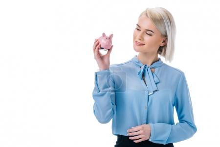 portrait of smiling businesswoman showing piggy bank isolated on white