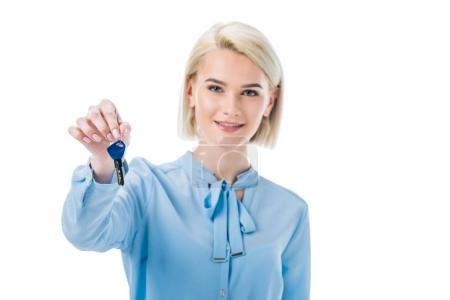 smiling female realtor holding key from new home, isolated on white