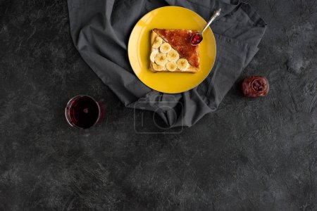 top view of toasts with banana slices and jam for breakfast on plate on dark tabletop