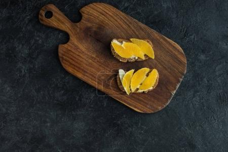 top view of snacks with orange pieces for breakfast on cutting board on dark surface
