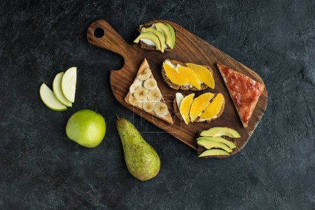 flat lay with snacks for healthy breakfast with fruits on wooden cutting board on dark tabletop