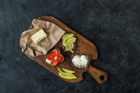 flat lay with snacks for healthy breakfast on wooden cutting board on dark tabletop