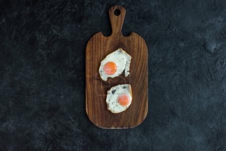 top view of fried eggs on wooden cutting board on dark surface