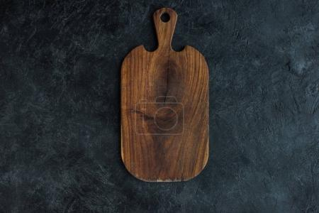 Photo for Top view of empty wooden cutting board on dark tabletop - Royalty Free Image