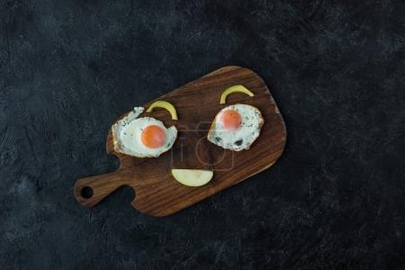 top view of smiling face made of food for healthy breakfast on cutting board