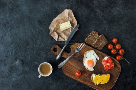 flat lay with tasty healthy breakfast on wooden cutting board on dark tabletop