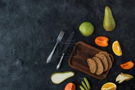 flache Liege mit Zutaten für gesundes Frühstück auf dunkler Tischplatte