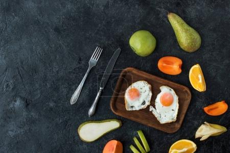 flat lay with healthy breakfast with fried eggs and fruits on dark tabletop