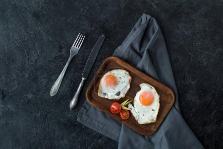top view of fried eggs with cherry tomatoes slices for breakfast on dark tabletop