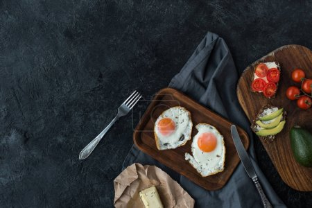 top view of fried eggs and healthy snacks for breakfast on dark tabletop