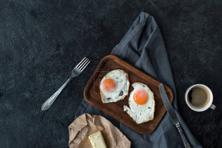 vue de dessus des œufs frits, le beurre et tasse de café pour le petit déjeuner sur table sombre