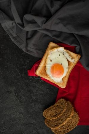 top view of fried egg on toast and slices of bread on dark surface