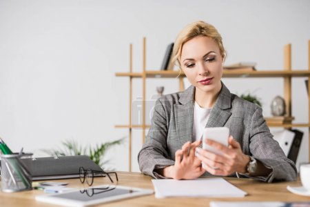 focused businesswoman using smartphone while sitting at workplace in office