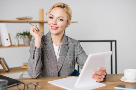 portrait of smiling businesswoman with digital tablet at workplace in office