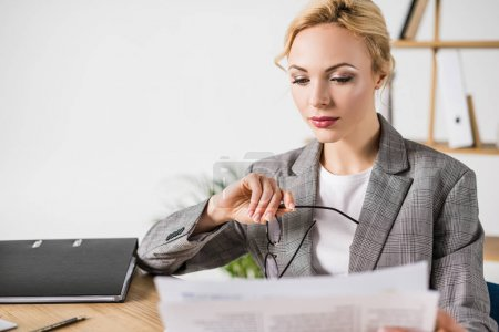 businesswoman with eyeglasses in hand reading newspaper at workplace