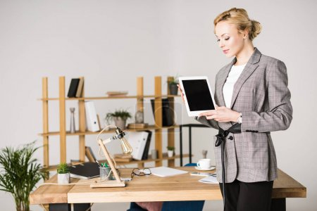 Photo for Portrait of confident businesswoman with tablet standing at workplace in office - Royalty Free Image
