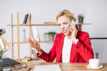 Photo for Portrait of angry businesswoman talking on smartphone at workplace in office - Royalty Free Image