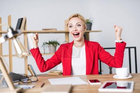 Photo for Portrait of happy businesswoman sitting at workplace - Royalty Free Image