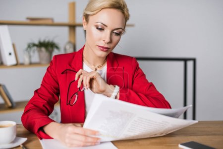 portrait of focused businesswoman reading newspaper at workplace