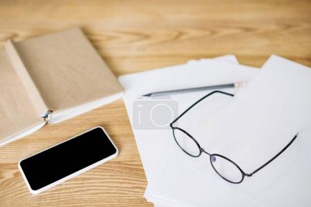 selective focus of smartphone with blank screen, eyeglasses and papers on wooden tabletop