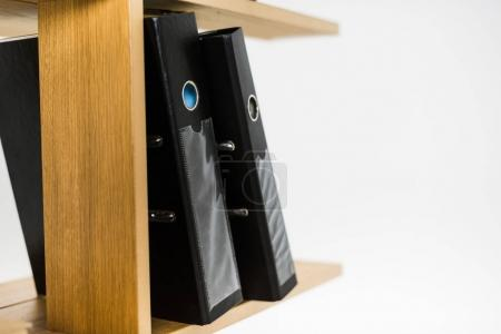 close up view of folders with documents on wooden bookshelf
