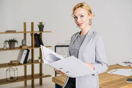 portrait of attractive businesswoman with folder in office