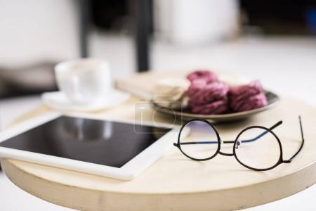 close up view of digital tablet, eyeglasses and zephyr on wooden tabletop