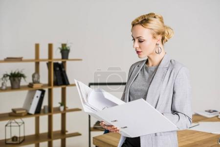 Photo for Portrait of attractive businesswoman with folder in office - Royalty Free Image