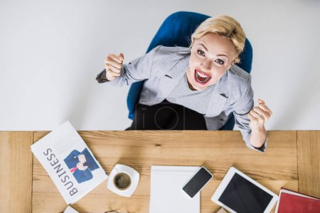 overhead view of excited businesswoman looking at camera at workplace in office