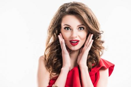 surprised girl in red dress touching face with hands isolated on white