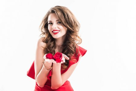 Photo for Smiling attractive girl showing red rose petals in hands isolated on white - Royalty Free Image